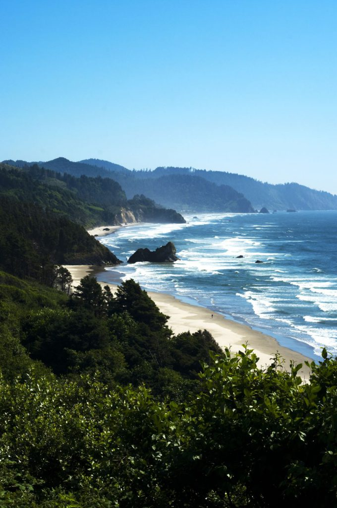 View from high above of green hills meeting sandy beach and crashing ocean waves below