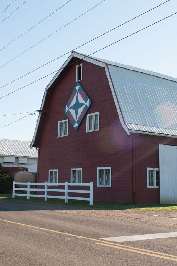 Exterior of red barn with a wooden quilt block facing the road