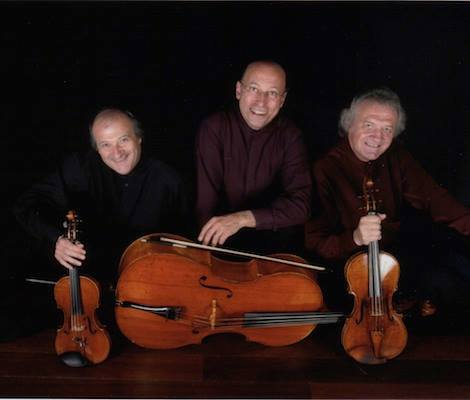 Three musicians pose with string instruments in front of a black background