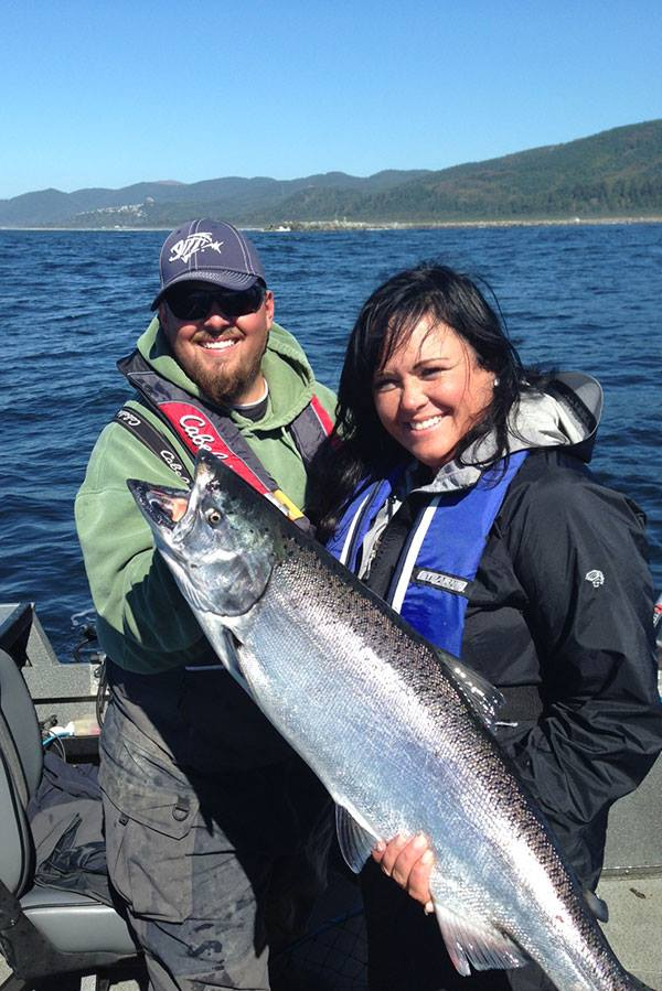 Man and woman show off big fish in a boat