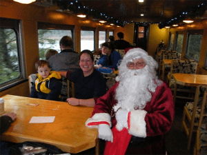 Santa sits with woman and child on a train