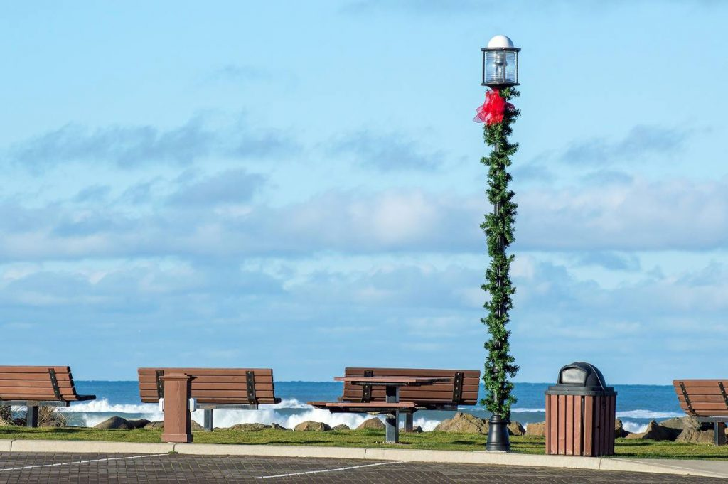 Lamp post on the beach with pine branch and bow decoration for the holidays
