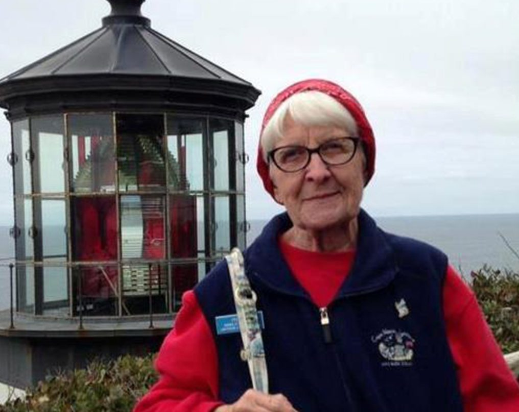 Oregon Coast Lighthouse keeper stands in front of lighthouse - woman wearing glasses and red hat