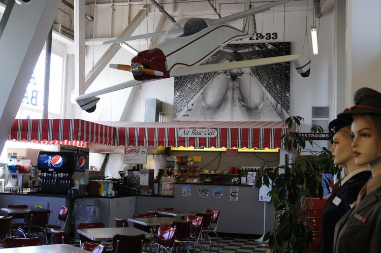 Air Base Cafe with soda machine behind bar, plane hanging overhead