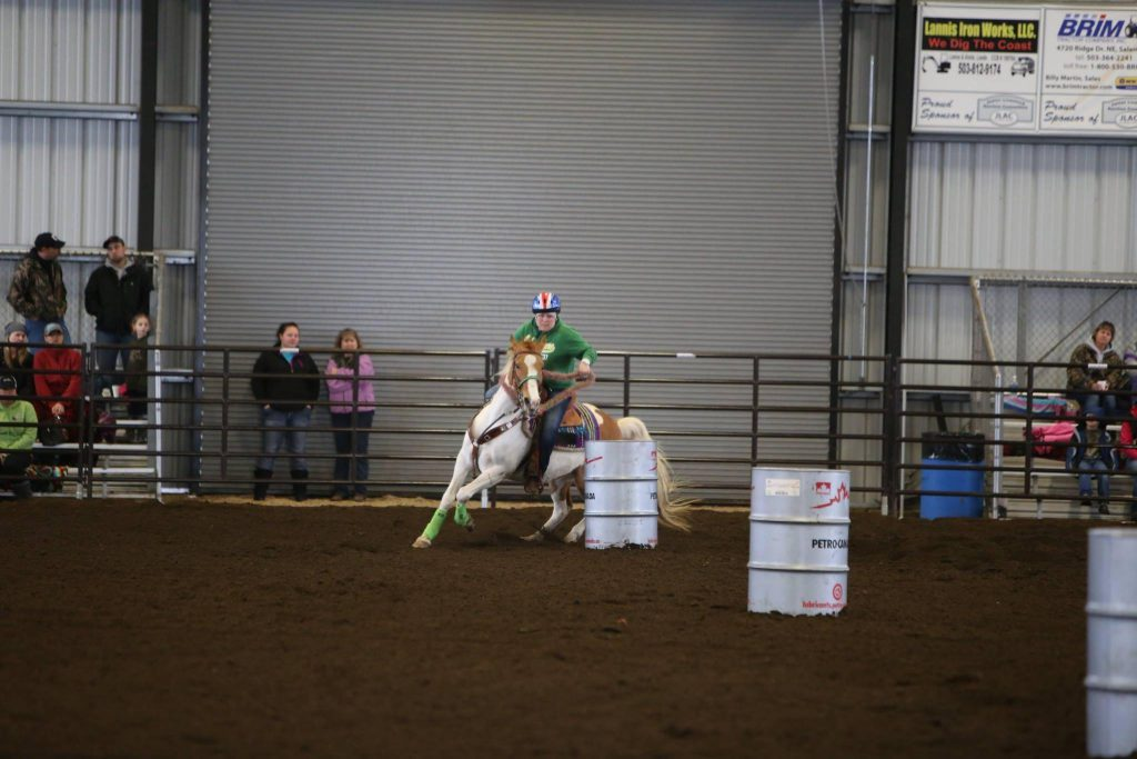 Horse and rider weave between barrels in the arena