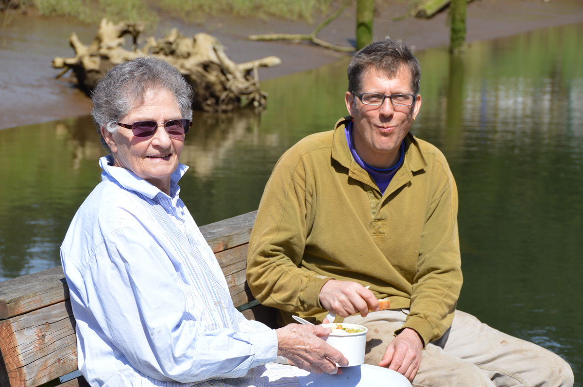 Older couple eating soup by the water