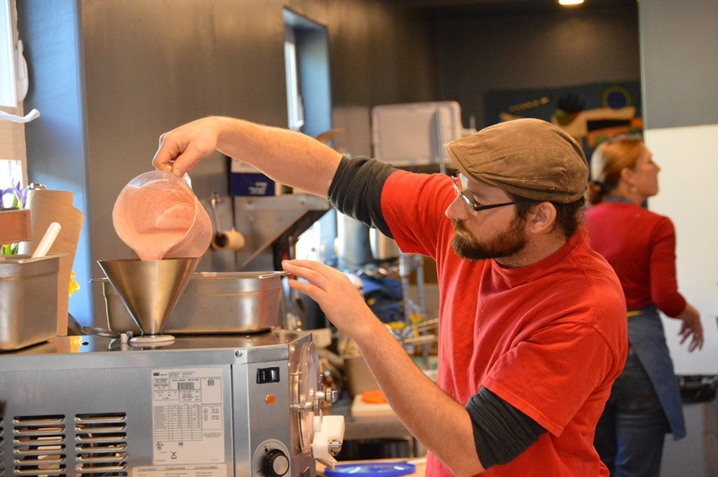 Buttercup employee pours mixture into ice cream machine