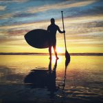 Silhouette of a person holding an oar and a paddle board in front of the sunset