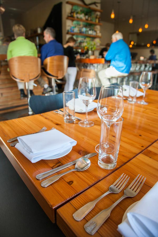 Wooden table in restaurant set with silverware and wine glasses, people sitting on bar stools in background