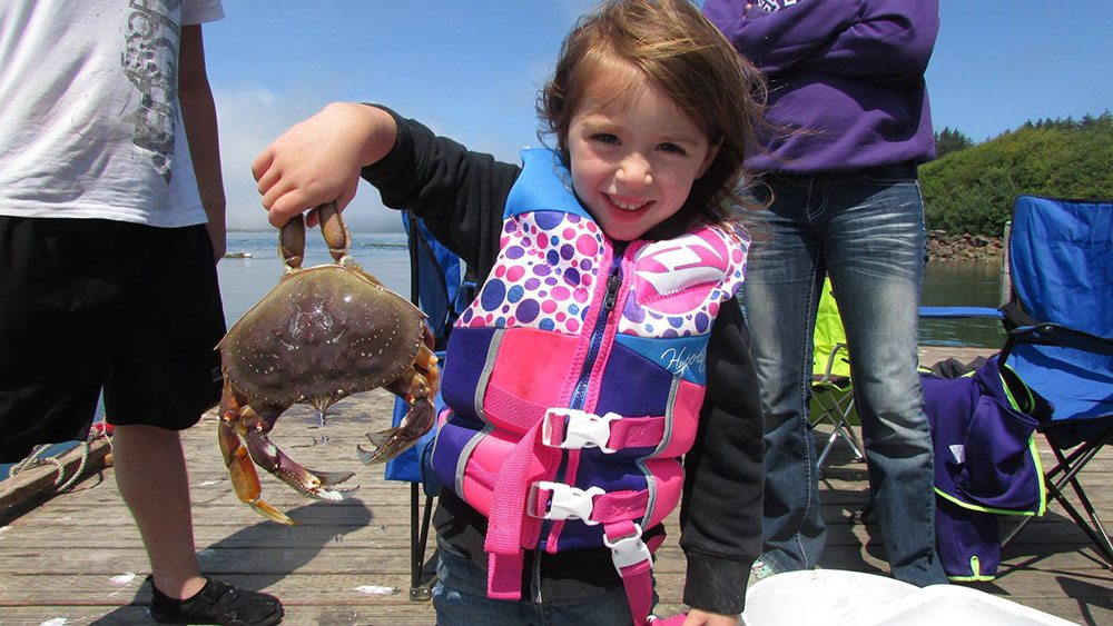Girl holding crab at Kelly's Brighton Marina