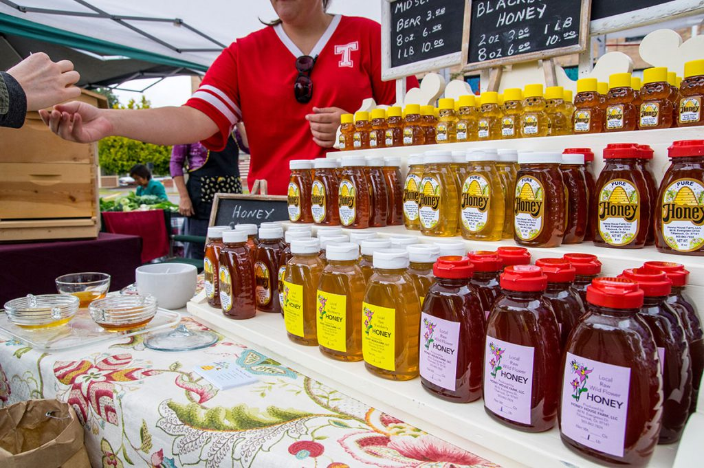 Different varieties of honey at farmers market stand