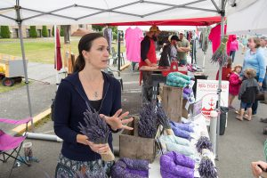 Vendor at farmers market tent arranges lavender and pillows