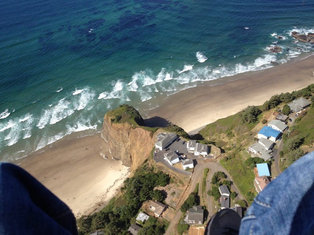 View through photographers feet looking down on the ocean and beach town