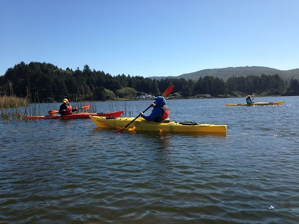 Three people in kayaks paddle in the lake