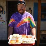 Man in tie-dye shirt holds a tray with chowder in bread bowls