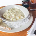 Bowl of chowder served with bread and beer