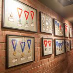 Framed medals lined up on a brick wall