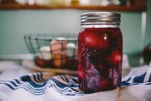 clear glass filled mason jar with lid on white and blue textile
