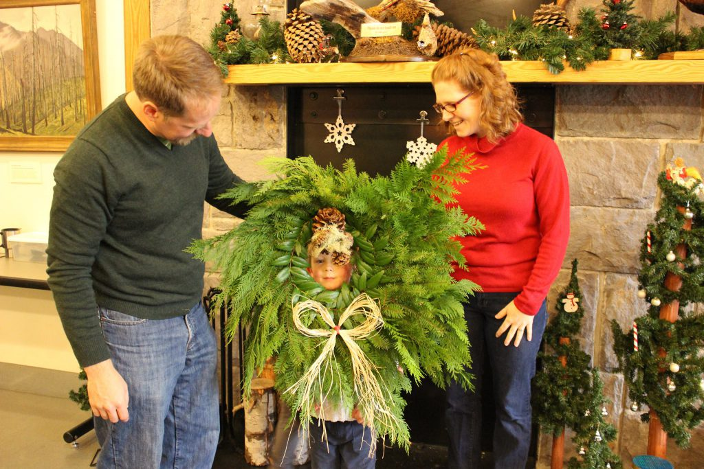 Man and woman stand around child with Christmas wreath around his head