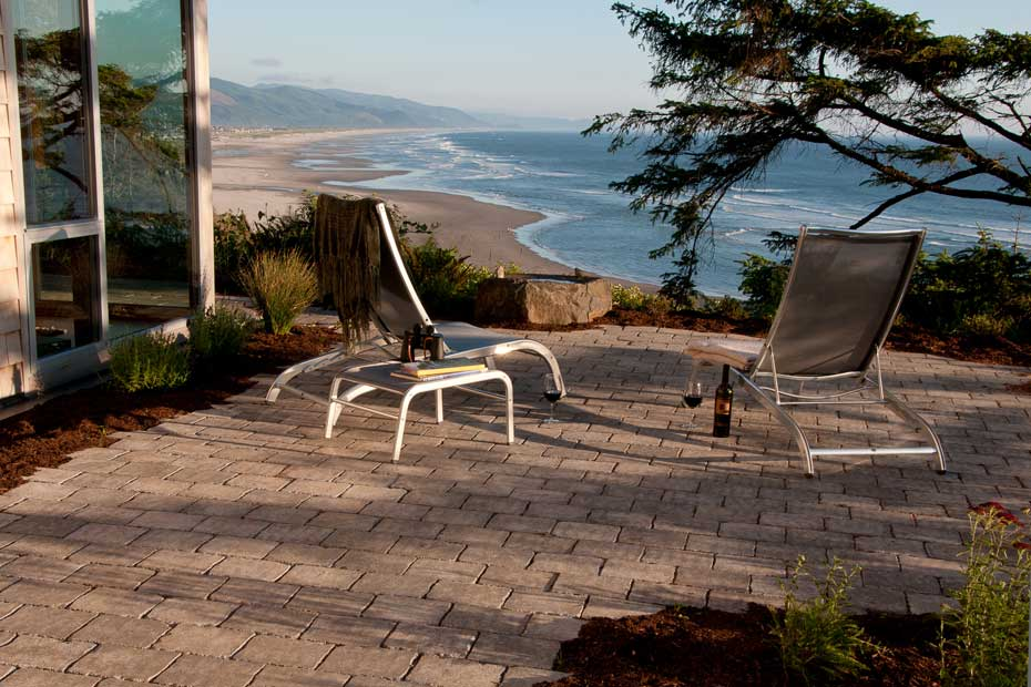Paved patio area with lounge chairs and a bottle f wine, overlooking the beach