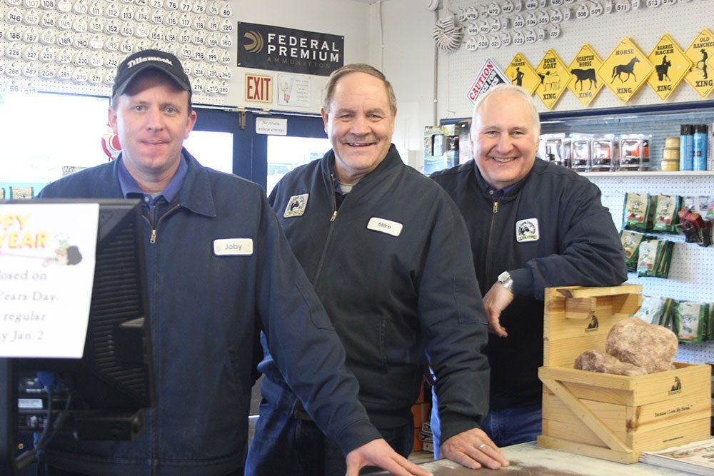Three men in blue uniforms stand in the TCCA Farm Store