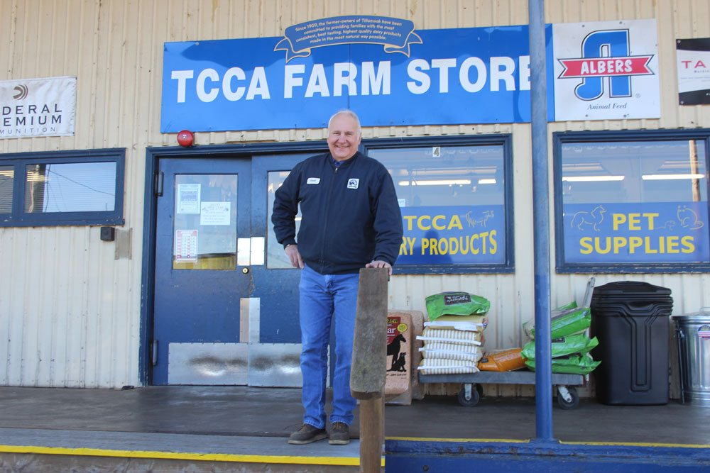 Man stands outside TCCA Farm Store sign