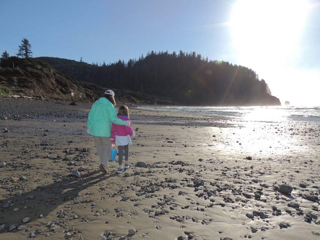 Woman and child walk along rocky beach at low tide