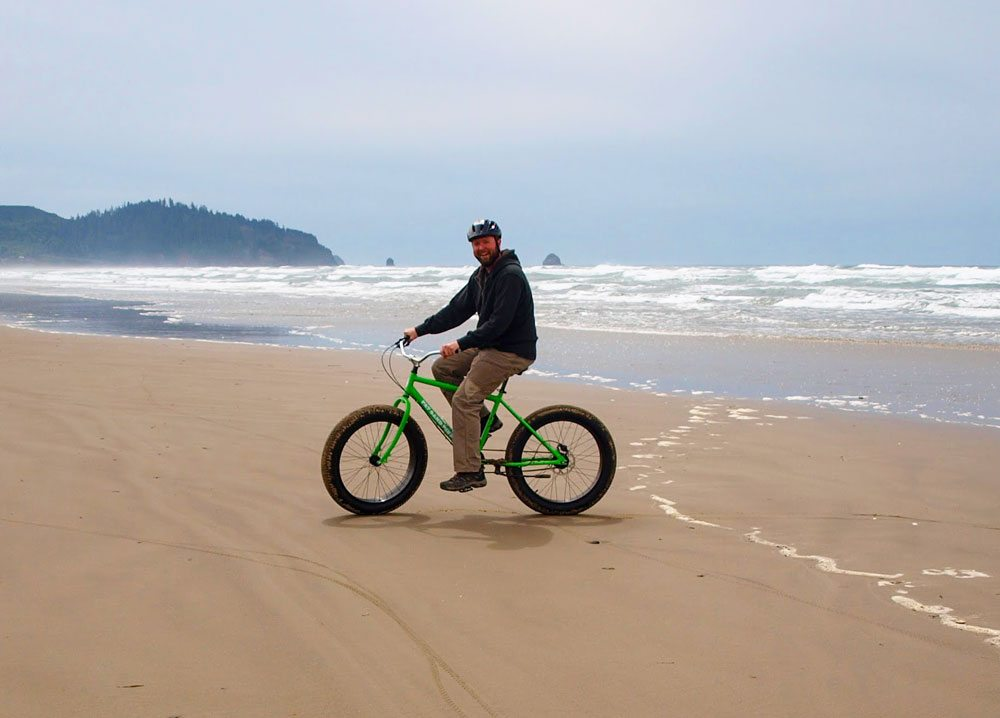 Man on fat-tire bike riding in the surf along the sand