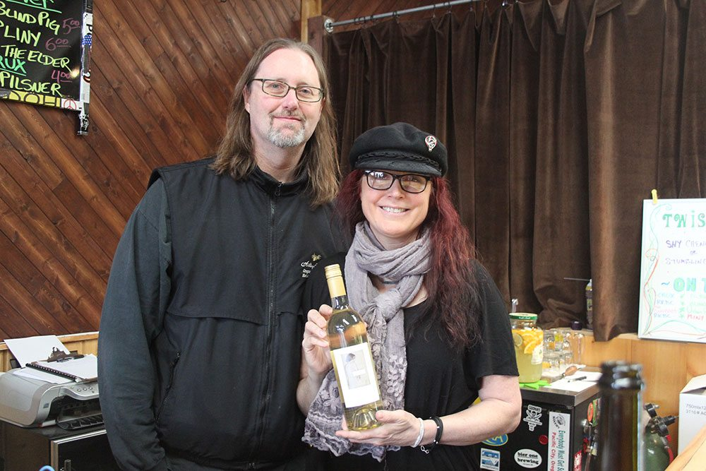 Man and woman both wearing glasses show off bottle of white wine