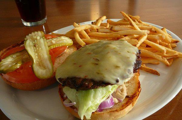 Open-faced cheeseburger with pickles, tomatoes, lettuce, onions and a side of fries