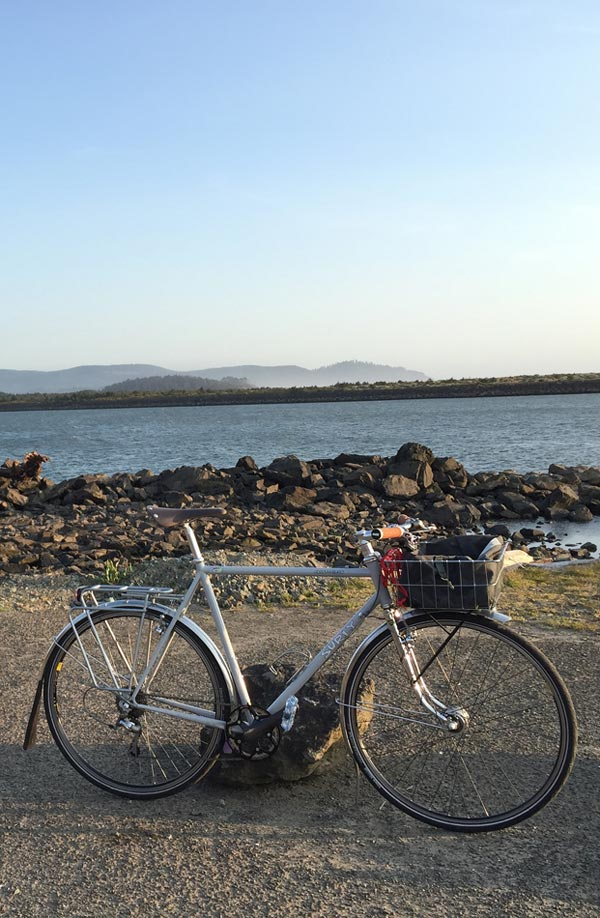 Bike parked on a gravel road next to the water