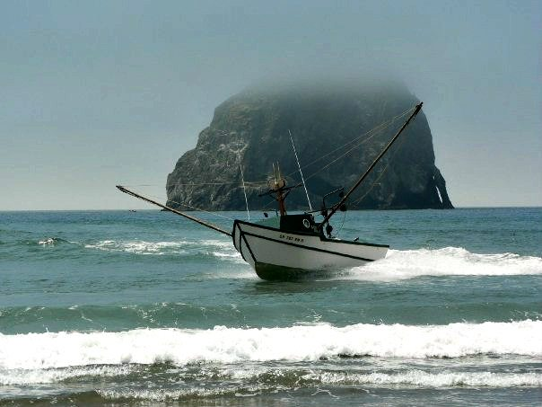 Dory boat on the water in front of Haystack Rock