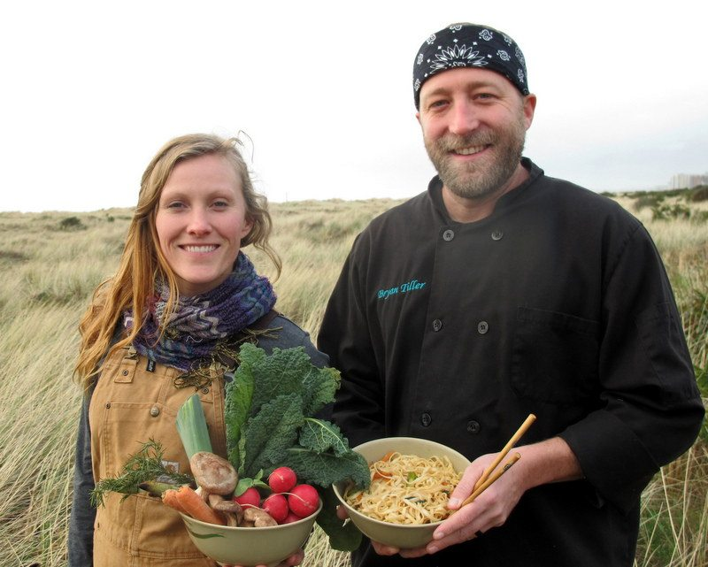 Man and woman standing on dunes holding fresh produce and noodles