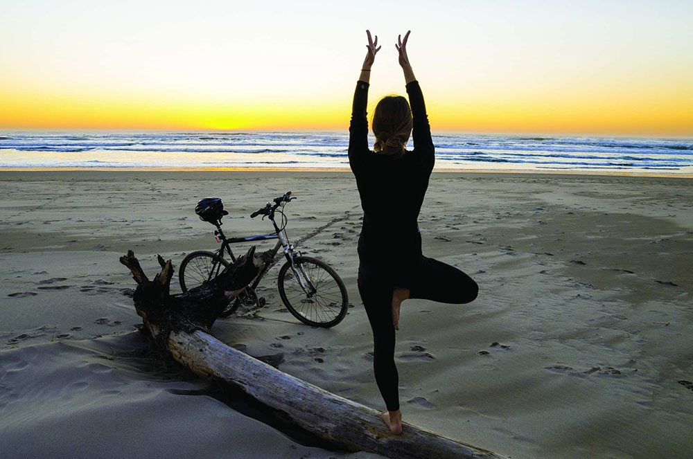 Person in tree pose on the beach at sunrise