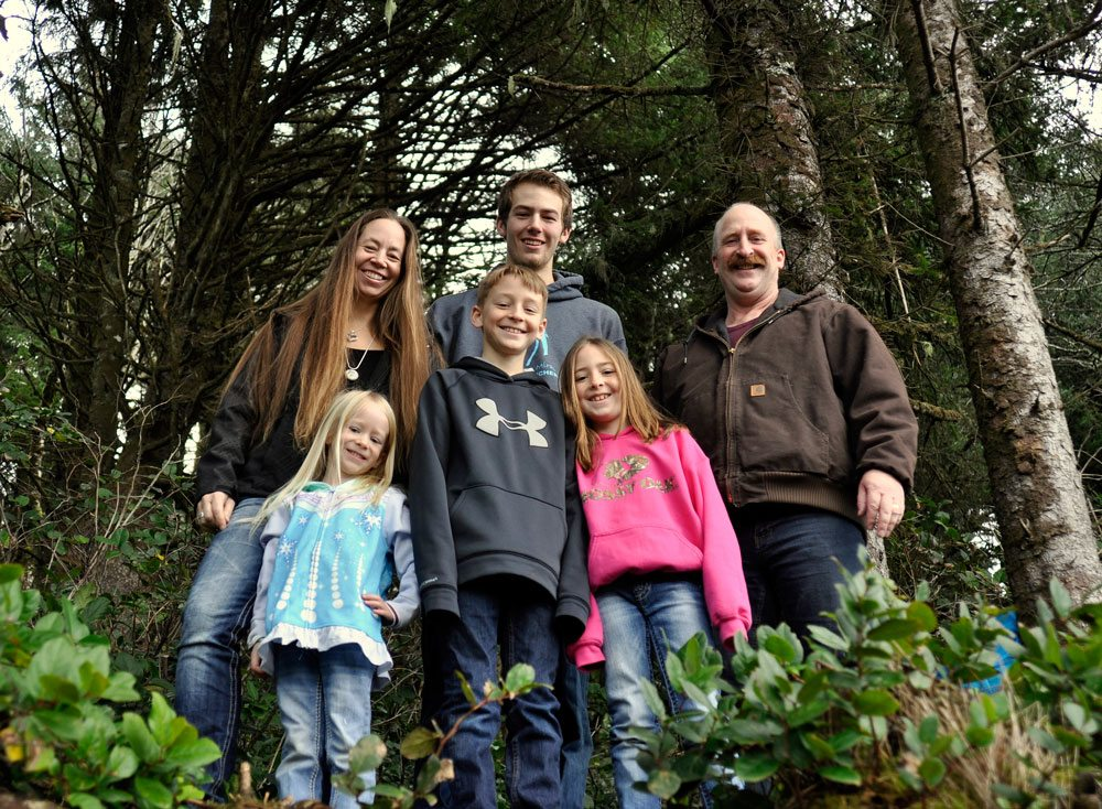 Happy group poses in the woods while geocaching in Tillamook County