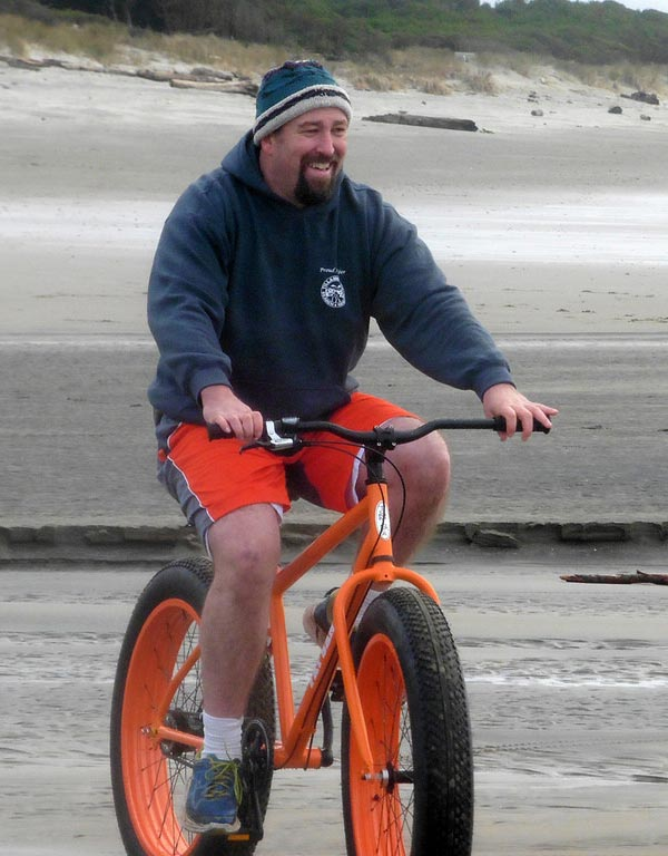 Man rides a fat tire bike on the sand