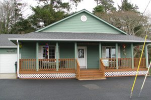 One-story, green house with porch