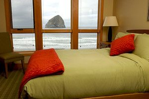 Bed with green blanket in cottage room overlooking the ocean