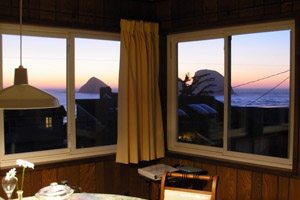 Room with windows overlooking the ocean at sunset