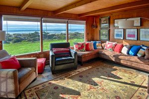 Living room with colorful couch cushions, area rug and big windows overlooking the ocean