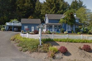 Blue house with white picket fence and long driveway