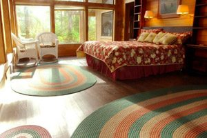Bedroom with colorful rugs and big windows