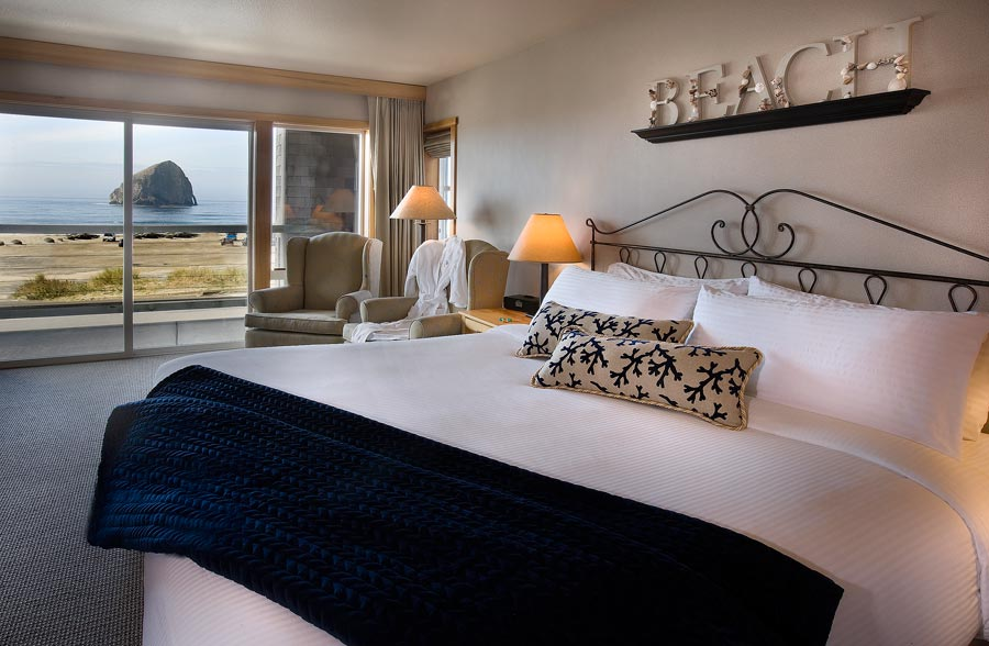 Bedroom with view of Haystack Rock through window, BEACH sign above bed