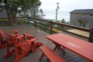 Red lounge chairs and table on balcony overlooking the ocean