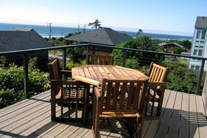 Chairs and table on balcony with view of the ocean