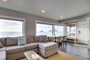Gray living room with long couch, dining table and windows looking out on the ocean