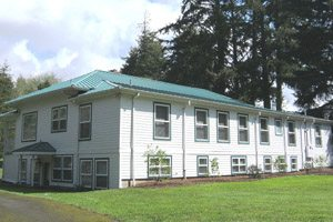 Long white building next to pine trees