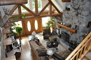 Interior of the Ranch House: living room with stone facade and exposed logs.