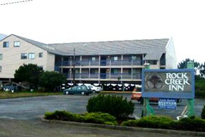 Outside of the Rock Creek Inn, beige building with long outdoor corridors, parking lot and sign