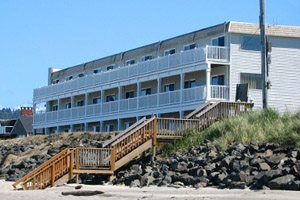 Long building off the beach with balconies in front of ocean-facing rooms
